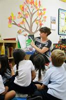 Kindergarten students listen to a story and talk about it with their teacher.