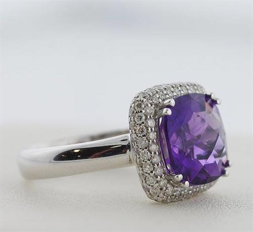 This 4.04 carat grape purple amethyst is an amazing color and has been cut in to a plump square cushion shape. It is surrounded by a pave set diamond halo.