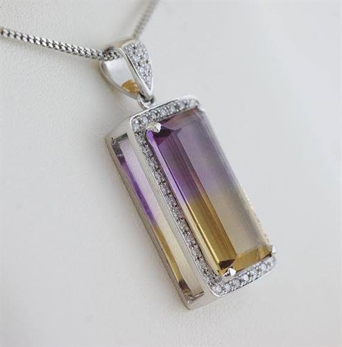 This Ametrine and Diamond Pendant is a rare and remarkable 8.98 carat stone that sits inside .34 carats of diamonds in 18 karat white gold.