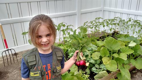 A happy harvester with her Raising Rochester beds on the back porch.