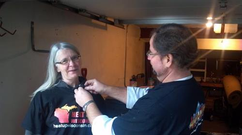Chris Pramas pins on a micro phone for Heat Up Recipient Cheryl Brock before her interview with NBC 15.  Cheryl was nominated and received a free furnace from Lennox Industries and Accu-Clime Mechanical Services LLC to have a free furnace installed in her home October 6th, 2012.