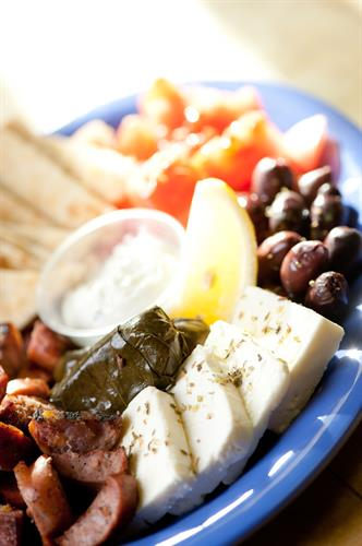 Meze Appetizer Plate. Feta cheese, kalamata olives, tomato wedges, stuffed grape leaves, loukanico (Greek Sausage), pita wedges and tzatziki sauce.