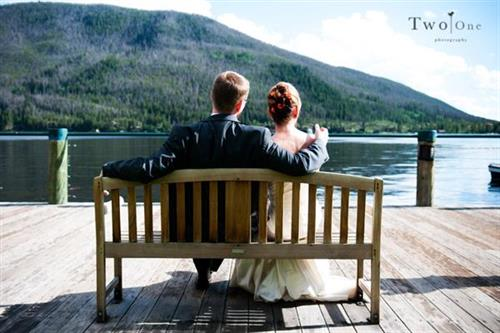 Bride & Groom sitting on bench located on boardwalk in front of Western Riviera Lakeside Event Venue