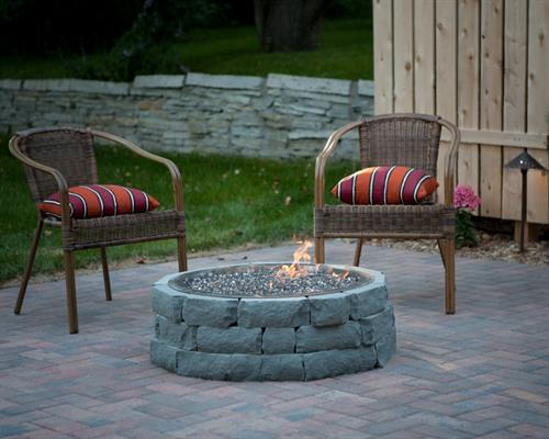 A paver patio, fire pit, and landscape project completed by Barrett Lawn Care