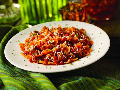 Mama Meata® Bow Tie Pasta.  Our famous pizza made pasta style! Diced pepperoni, spicy Italian sausage, meatballs and bow tie pasta tossed in a Bolognese sauce and topped w/ Parmesan cheese!