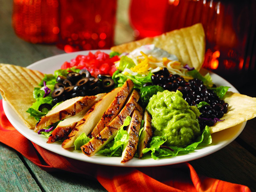Sante Fe Salad.  Your choice of grilled chicken breast or flat iron steak on fresh mixed greens tossed w/ our Sante Fe dressing. Topped w/ black beans, tomatoes, cheddar cheese, black olives, sour cream and guacamole and crispy tortilla wedges.