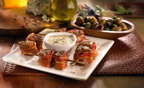 Bacon Wrapped Steak Skewers.  Grilled flat iron steak wrapped in smoked bacon. Served with our bleu cheese cream sauce.