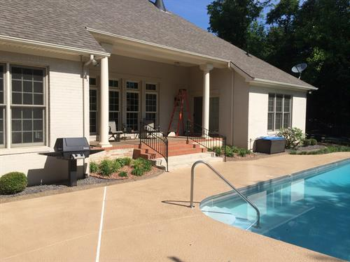 We leveled out the area in front the steps and refinished the entire pool deck with a colored sealant.