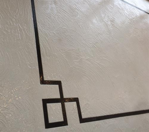 This is a Roman Key border in Pepper Black and Arctic Stone.  It is finished with a clear coat sealant.