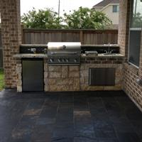 Outdoor kitchen with slate tile flooring