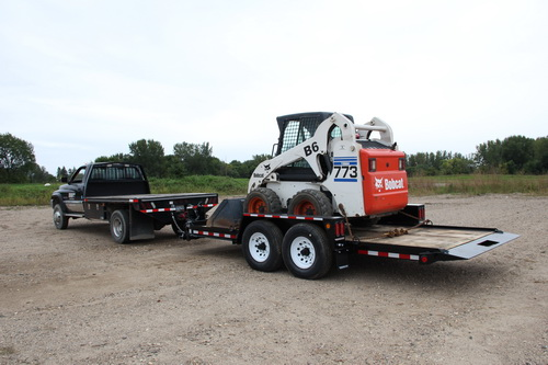 Tilt bed trailer with skid-loader.