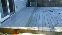 Dirty composite deck being power washed