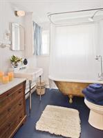 Bathroom with a golden claw foot tub + rain shower, spa towels and robes
