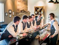 Groom with groomsmen in the distillery.
