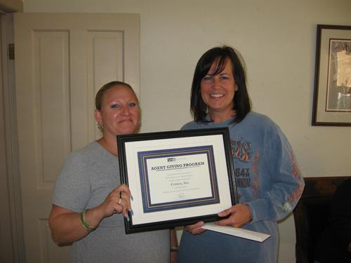 Employee, Lisa Sheheen, gives donation from Safeco to Robin Zimmer for COMEA