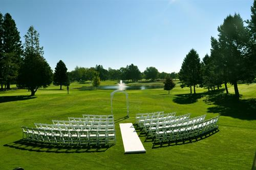 Ceremony Site in Ludington with our White Resin Chairs and Wood Arch