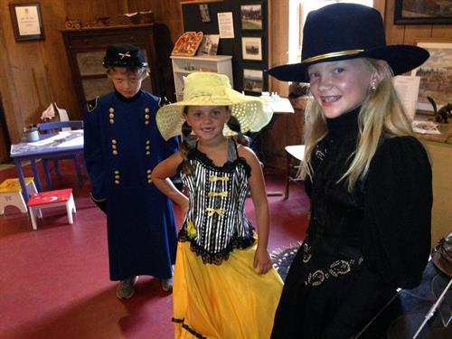 visitors trying on historic costumes at the museum