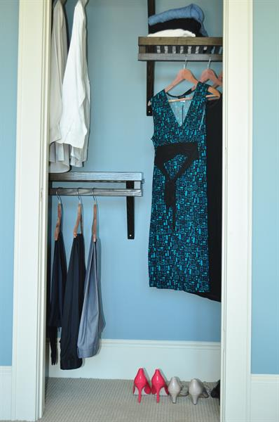 Reach in closet with high and low hanging areas, plus shelves