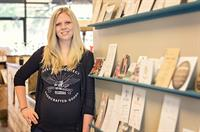 Toni next to our wide variety of custom stationery & wedding invitations