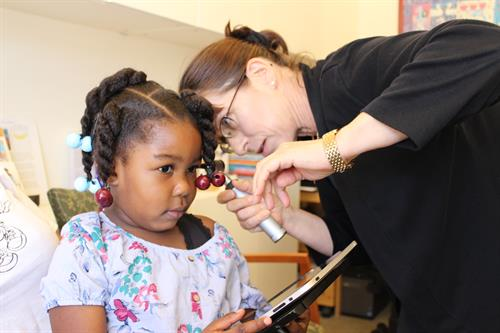 A young student has her hearing tested.