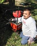 Granite Foundation Repair employee using hydraulic pump to drive piers