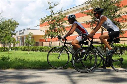 Bicyclists ride by Ocoee High School