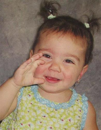 2 year old child signs to her parents She wears hearing aids in both ears