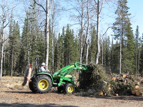 John Deere tractor with brush grapple and logging winch