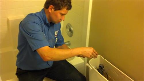 Plumber Matt works on a toilet
