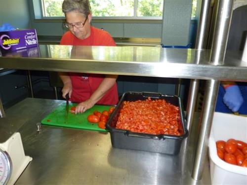 Volunteer Processesing Donated Tomatoes