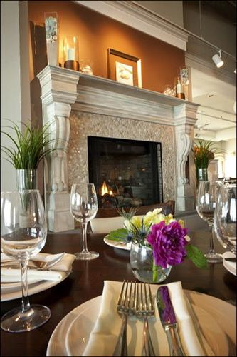 "An elegant stone fireplace is a focal point in the relaxed ""beach chic"" dining room."