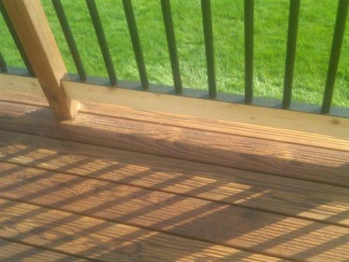 This is thermally treated wood. It is brown all the way through and doesn't need any staining for several years. Notice the railing system eliminates the need to stain between spindles.