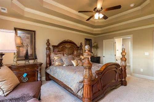 Inviting Master Bedrooms with tiered ceilings and warm lighting.