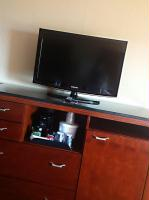 Guest suite television and granite, dark wood dresser