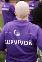 Cancer survivor wearing purple t-shirt at Relay event.