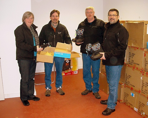 Kim Lacasse, Co-Chair accepts boots from Al Miltner, Bootleggers.  Board members Dennis Phelps and Chris Guilmett help