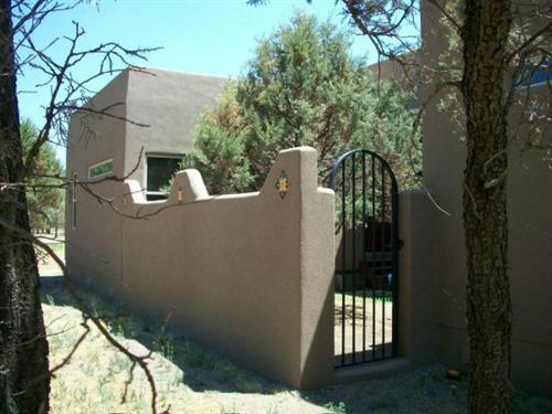 Synthetic stucco with custom inset tiles on private courtyard walls