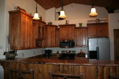 Custom cabinetry and granite counters with vaulted wood ceilings