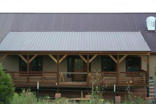 Custom redwood deck accents this barn style home