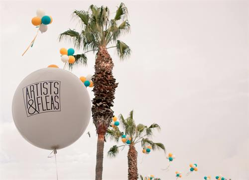 Palm trees and blue balloons line Artists and Fleas.