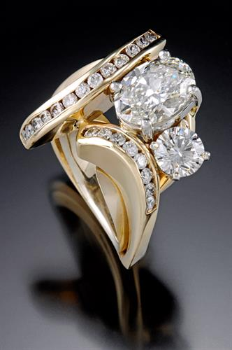 Custom designed ring incoroparating customer's original engagement diamond with a 2 carat center and channel set diamonds.