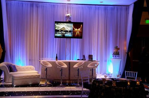 uplighting, sheer drapery, modern furniture, bar stools, leather chaise, LED screens