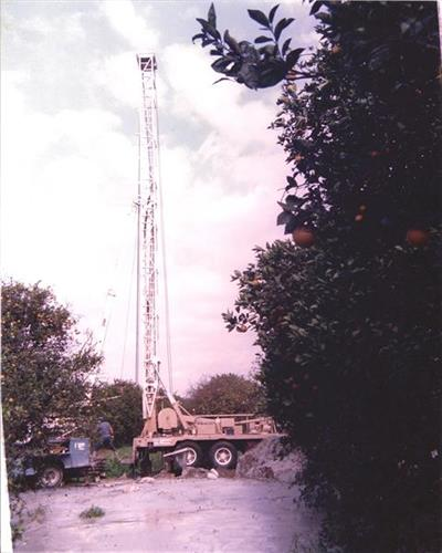 Ray R. Domer well drilling in an orange grove.