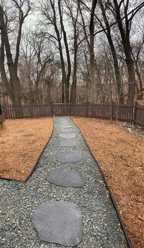 Landscape project from summer of 2020. This project including the existing landscaping, instaling drainage, a retaining wall, with mulch and rock for an easy access pathway for the homeowner.