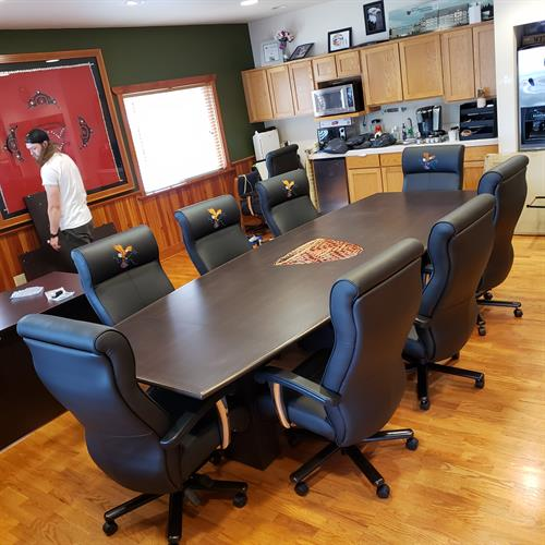 Custom Logo'd boardroom table with embroidered leather chairs