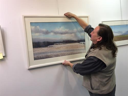 Artist Tom Tomasek hanging one of his pieces.