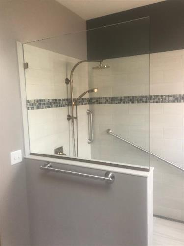Handicap accessible shower, no threshold shower wide enough for wheelchair movement, 1/2 wall with glass and niche in 1/2 wall for easy access.