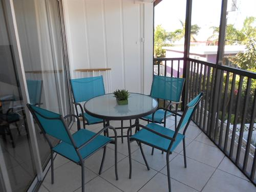 Views of lush vegetation and glimpses of the gulf are visible from the lanai.