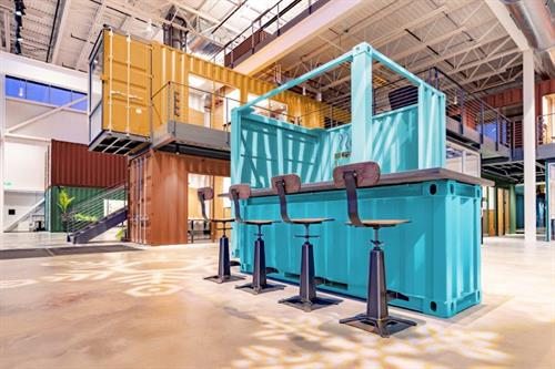 "A shipping container ""city"" within a building for a large, creative corporate office environment."