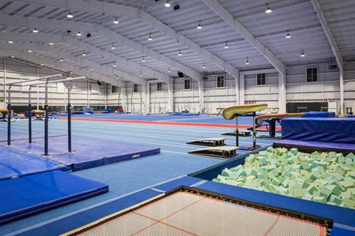 Facilities include 3 full-size spring floors, 4 loose-foam pits, a Eurobed trampoline, 2 40-foot tumble tracks, and 6 vault runways.